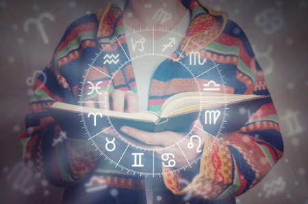 Joven leyendo un libro de astrología. Concepto de lectura de astrología y horóscopo. Foto de archivo