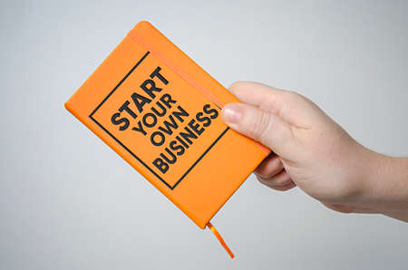 Start your own business information book in hand. Business concept. Stock Photo