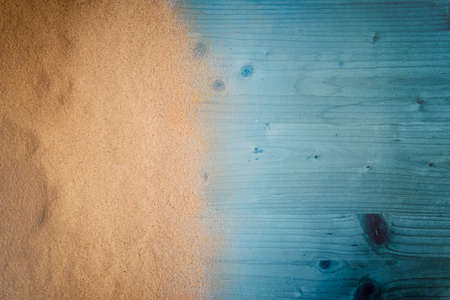 Beach background. Top view of beach sand on old wood plank. Summer vacation concept.