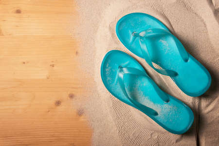 Summer holiday background with blue flip flops on  wood panel, top view with copy space
