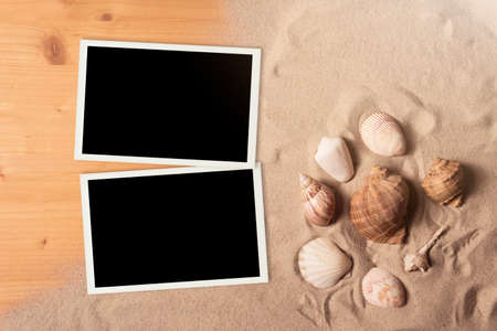 Empty photo cards lying on a sea sand. Sunny summer background.