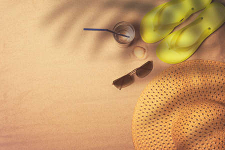 Flip flops, straw hat and sunglasses on a sandy background, top view