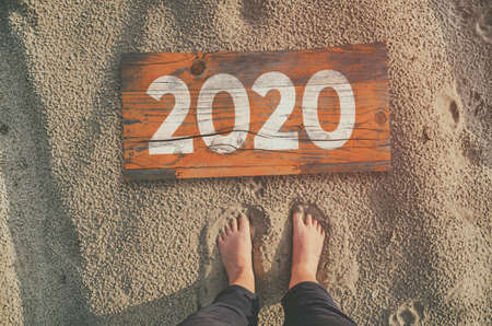 2020 wooden board on sandy beach, top view. Travel and vacation concept. Фото со стока