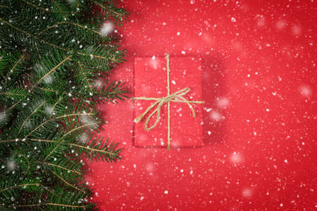 Christmas gift box on red background with snowflakes. Merry Christmas and Happy New Year composition.