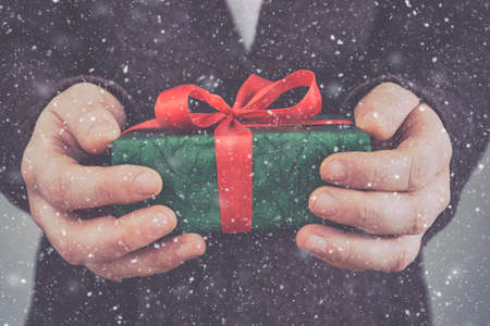 Merry Christmas and Happy New Year. Close up of Christmas gift box in male hands.