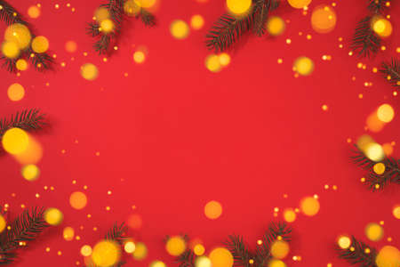 Christmas background with fir tree and sparkle bokeh lights on red background