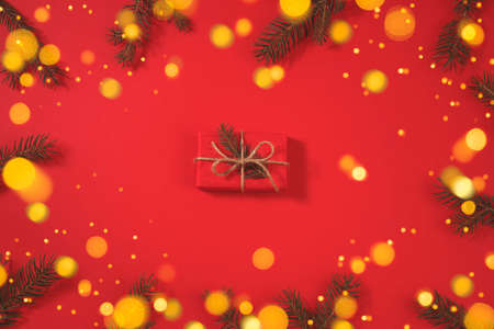 Gift box. Christmas background with xmas tree and sparkle bokeh lights on a red background.
