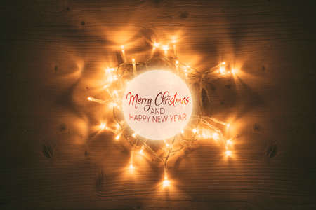 Christmas lights with glowing ball on wooden table background Фото со стока