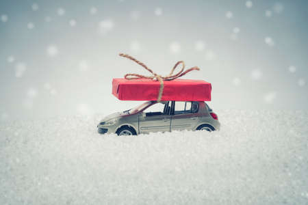 Christmas gift box on car toy with snow. Merry Christmas and Happy New Year concept. Snow effect added. Фото со стока