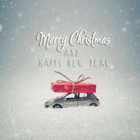 Merry Christmas and Happy New Year card. Christmas gift box on toy car with snow. Snow effect added. Фото со стока
