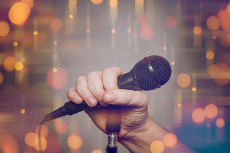 Male hand and microphone on the stage with blurred lights