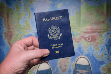 Time to travel. Man holding US passport on the world map background. Personal perspective. Фото со стока