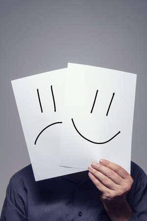 Man holding paper with smiley and sad faces in front of his head, studio shot. Фото со стока