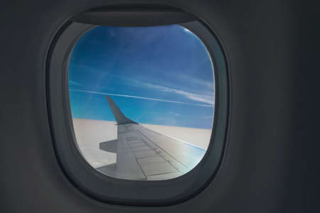 Airplane window. Traveler air plane and vacation traveling concept. Imagens