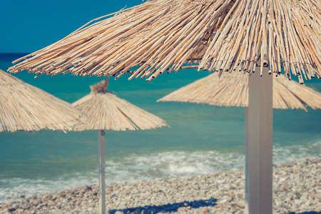 Straw umbrella on beautiful beach background close. Selective focus.