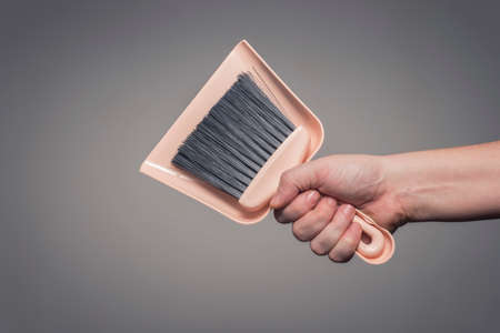 Male hand holding dustpan and brush set. Cleaning service and maintenance concept.