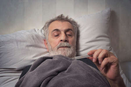 Sick man in bed with a thermometer