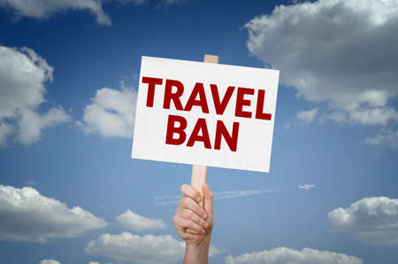 Travel ban message on board in hand with sky background Stock Photo