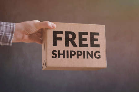 Deliveryman gives Free Shipping carton box. Free shipping business concept. Stock Photo