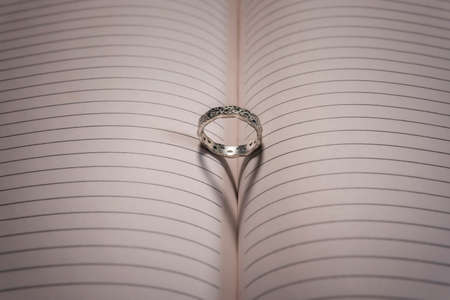 Wedding ring with shallow depth of field and heart shaped shadow.