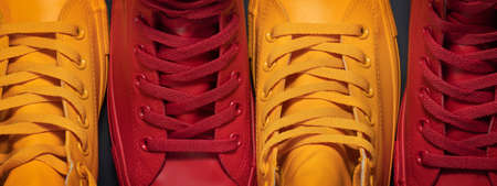 Diversity. Red and yellow sneakers standing by each other depicting the idea of diversity, unity and inclusion.