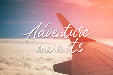 Adventure awaits inspirational quote on plane wing, blue sky and clouds background.