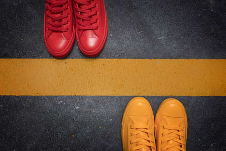 Social distancing concept - to avoid spreading of virus. Two people standing opposite each other divided by the yellow asphalt line, top view.