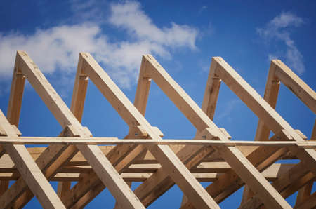 Roof construction. New residential construction home framing against a blue sky. Stock Photo
