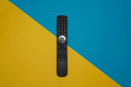 A modern TV remote control on yellow and blue pastel background. Top view, minimalism. Stock Photo