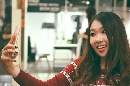 Young pretty Asian woman using her smartphone to selfie Stock Photo