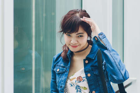 Young beautiful Asian woman smiling with outdoor scene in matte style.