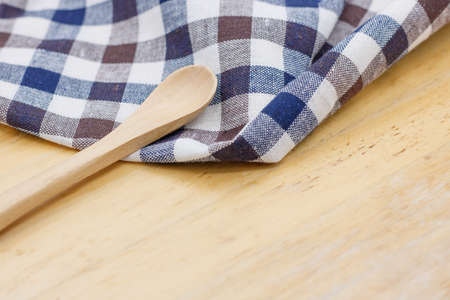 Kitchen napkin and spoon on wooden background