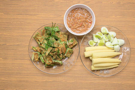 Top view of Acacia Pennata Omelette and Shrimp-paste sauce, vegetables on wooden background.