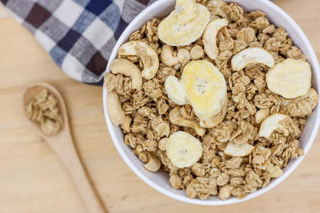 Granola with nuts and dry bananas in white blow on wooden table with wooden spoon and cute fabric.