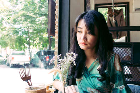 Beautiful Asian woman sitting in the cafe. Stock Photo