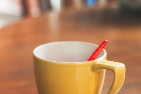 Yellow cup with red spoon on the table.