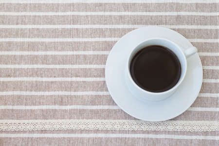 A cup of coffee on cute fabric.