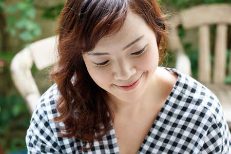 Close up of young attractive Asian woman with outdoor scene.