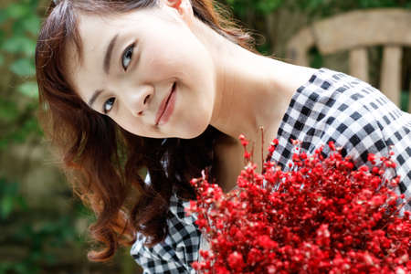 Young attractive Asian woman holding red bouquet. Relationship concept. Stock Photo