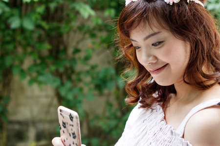 Young pretty Asian woman with flower headband using smartphone.