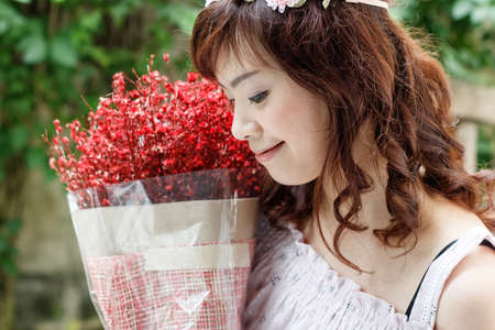Young pretty Asian woman wearing flower headband and holding red bouquet. Stock Photo