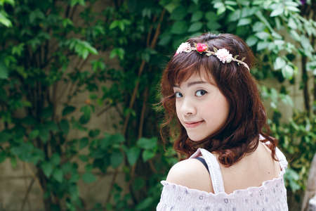 Young pretty Asian woman with flower headband.