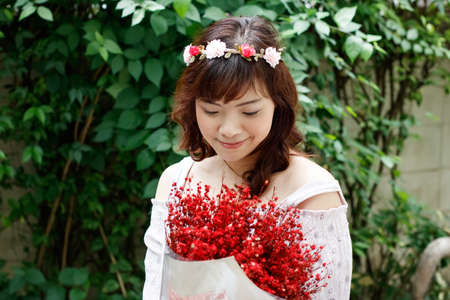 Young pretty Asian woman wearing flower headband and holding red bouquet. Stockfoto