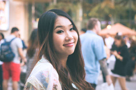 Beautiful Asian woman smiling with outdoor scene. Stock fotó
