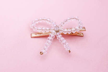 Luxury crystal hair clip on pink fabric with copyspace.