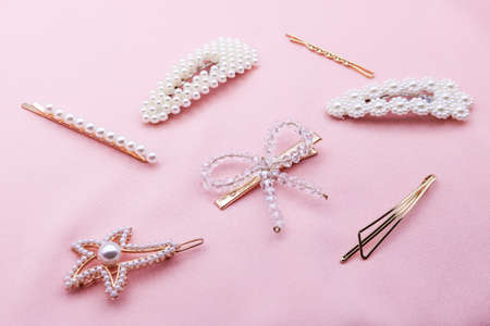 Luxury hair clips on pink fabric with copyspace. Фото со стока