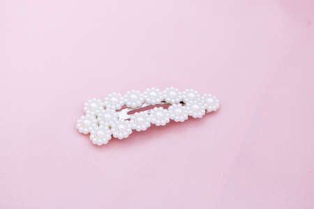 Luxury hair clip on pink fabric with copyspace.