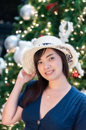 Pretty Asian woman with blur Christmas light background.