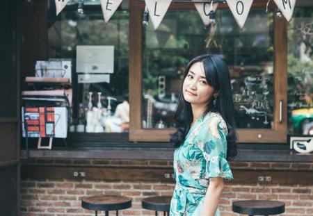 Beautiful Asian woman smiling in outdoor scene.