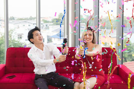 Young and attractive couple celebrate Christmas and new year with confetti poppers.